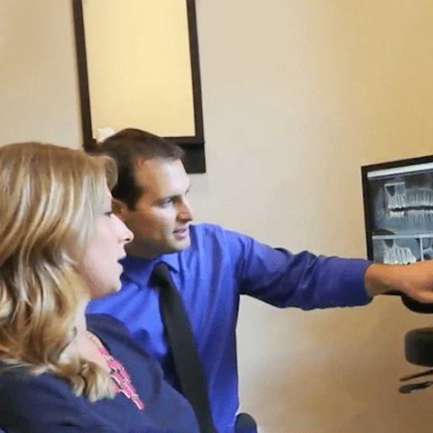 Your dentist in Prescott, AZ pointing at an xray screen and working with a patient to help achieve a better smile