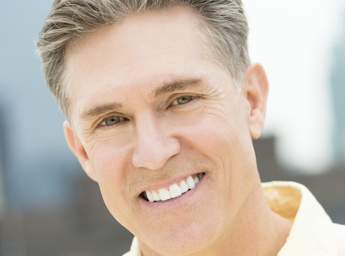 A man shows off his smile to show how dental Extractions can be used to enhance hour smile