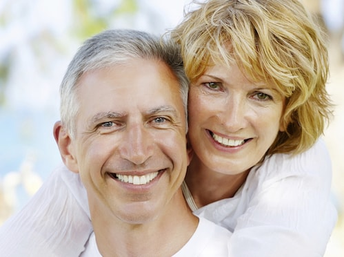 An older couple smiling shows how Inlays and Onlays can repair decayed or fractured teeth