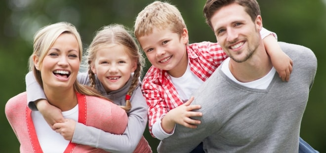 A mother and father smiling and playing with their kids shows how restorative dentistry can bring back your smile.