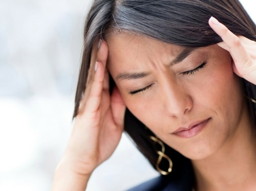 A woman holding her temples show how TMD Therapy can help alleviate headaches