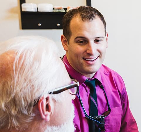 Dr. Paul Wulff discusses same-day dentistry options with an older male patient.