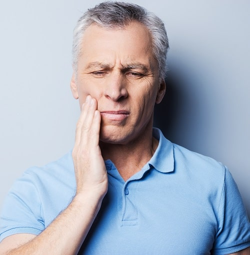 A man holding his painful jaw in need of TMJ treatment from our Prescott experts.