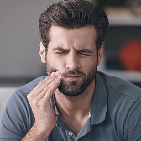 A man holding his jaw because of severe tooth pain